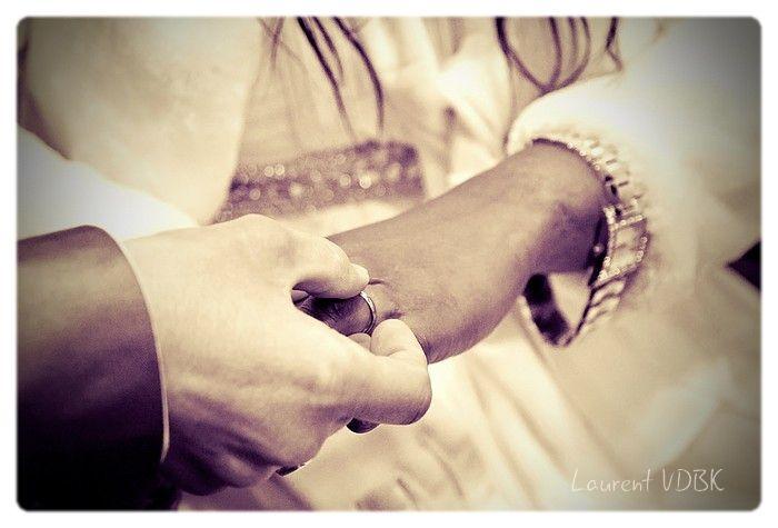 Cérémonie civile de mariage : le marié passe l'alliance au doigt de la mariée. Traitement en style rétro/ancien (technique du virage partiel sur photo noir et blanc)