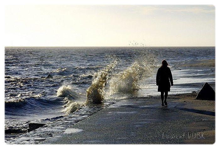 Passant qui se prommène sur la digue alors que la mer est très haute (grande marée) et que les vagues s'éclatent. Ne semble pas craindre les gerbes d'eau. Photo à contre jour.