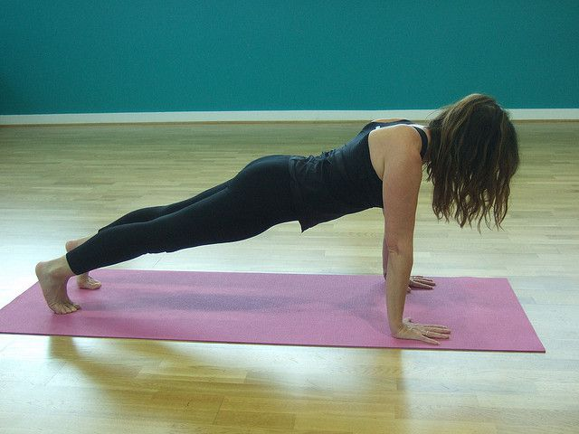 10) Kumbhakasana or plank pose:- Benefits:-→ It strengthens and tones your arms, shoulders, back, buttocks, thighs and abs. note:-If you have back or shoulder injuries or have high blood pressure avoid doing this pose. Steps to do this pose:- 1)Lie flat on your tummy on the floor or your yoga mat. 2)Now place your palms next to your face and bend your feet so that the toes are pushing off the ground. 3)Push off your hands and raise your buttock into the air. 4)Your legs should be flat on the floor as far as possible and your neck should be loose. This is known as the downward dog or adho mukha svanasana. 5)Once here, inhale and lower your torso so that your arms are perpendicular to the floor and your shoulders and chest are directly over your arms. Remember to keep your fingers from flaring out and keep them close together. You will feel your stomach muscles tighten. Hold this pose for as long as you can. 6)To get out of this pose, exhale and gently lower your body to the floor. 7)You can end this pose by either doing bhujangasana or simply roll to your side and push off your hands to the sitting position.