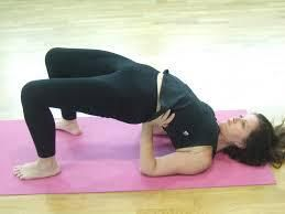 13) Setubandhasana or Bridge pose:-  Benefits:- → This pose is great to tone the thighs, strengthen the shoulders and tone your abs.  →It also relaxes the mind, improves digestion, relieves the symptoms of menopause in women and stretches the neck and spine.  →It is also great to keep one's blood pressure under control. Avoid doing this pose if you have a neck or back injury.  Steps to do this pose:- 1) Lie flat on your yoga mat, with your feet flat on the floor.  2)Now exhale and push up, and off the floor with your feet. Raise your body up such that your neck and head are flat on the mat and the rest of your body is in the air.  3)You can use your hands to push down for added support. If you are flexible you can even clasp your fingers just below your raised back for that added stretch.  TAKE CARE