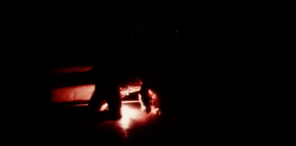 L'artiste s'enveloppe de câbles électriques où pendent des ampoules et va allumer l'ensemble. La salle est plongée dans l'obscurité.