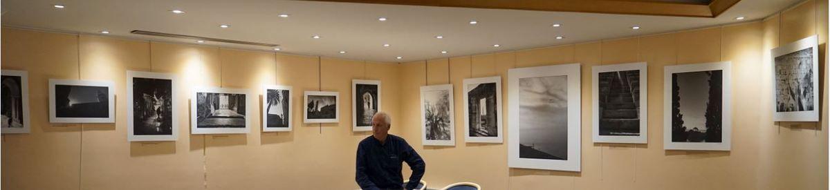 Le Photographe Jean-Pierre Germain devant une partie de ses clichés exposés à Cayenne de la GLNF.