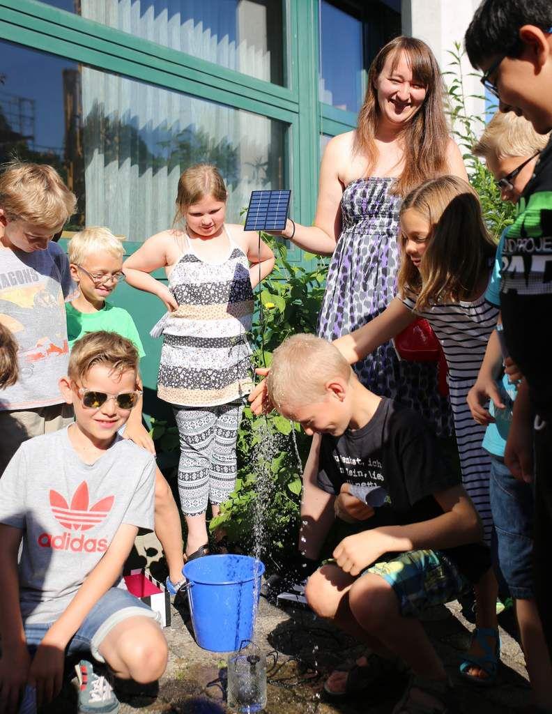 """""""Solarenergie zum Anfassen"""" hieß ein weiterer Workshop, bei dem eine, durch ein Photovoltaik-Tablet betriebene Pumpe eine Wasserfontäne in die Höhe befördert. Auch hier konnten die Kinder bei der Hitze, die heute herrschte, wie schon beim durch das Energiefahrrad betriebenen Ventilator sich zugleich eine Abkühlung verschaffen."""