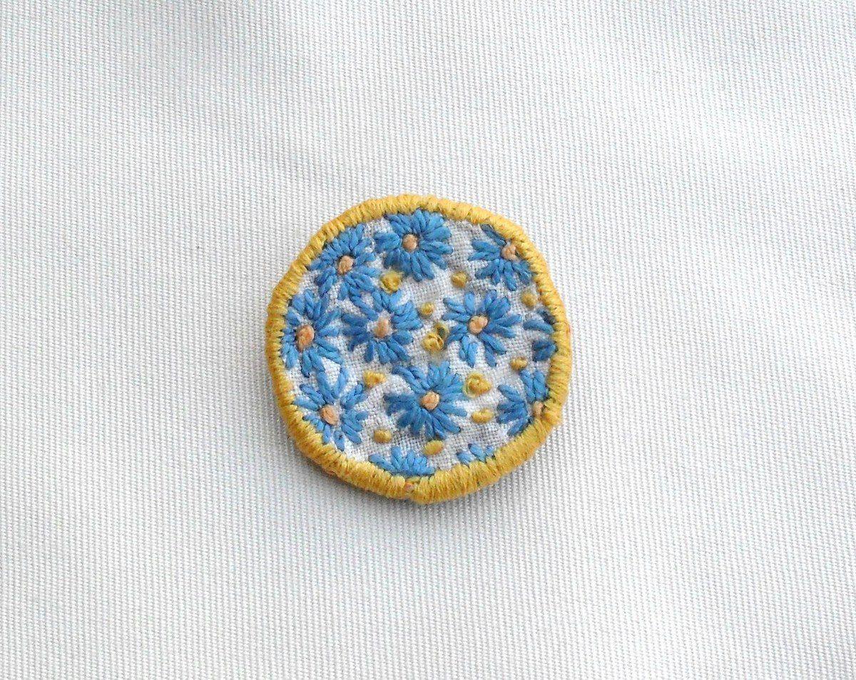 Broche ronde brodée à la main sur coton blanc. Motif central en broderie : fleurs bleues stylisées avec coeurs et entourage brodé en coton orange. Dos en cuir coté daim bleu, attache de couleur bronze. Dimensions 4.7 cm de diamètre