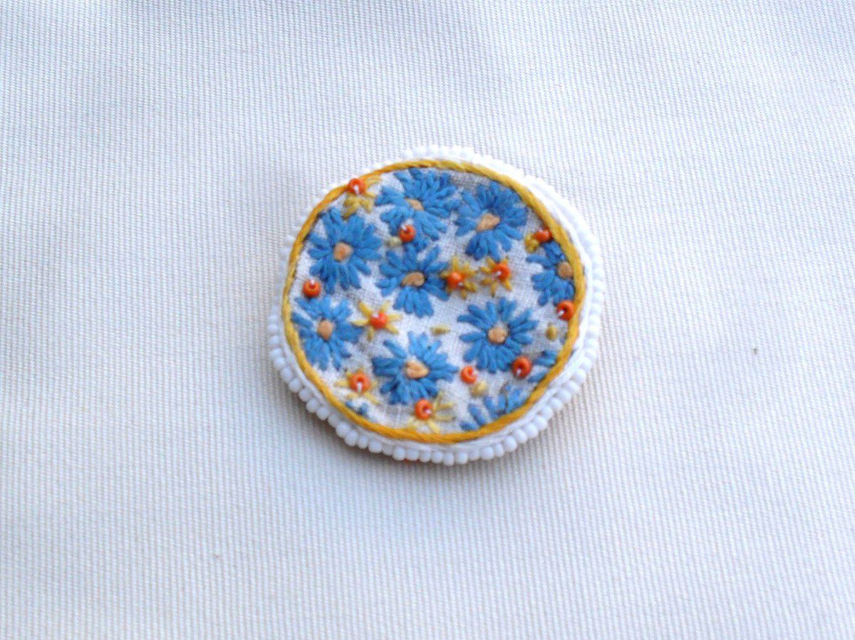 Broche ronde brodée à la main sur coton blanc avec entourage en perles de rocailles. Motif central en broderie et perles : fleurs bleues stylisées avec coeurs en perles de couleur orange. Tour de la broche en perles de rocailles blanches mates. Dos en cuir coté daim orange, attache de couleur bronze. Dimensions 4.7 cm de diamètre