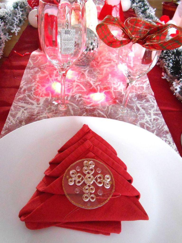 une boucle d'oreille décore un verre et un noeud décore l'autre. Une serviette et son rond de plexis/quilling