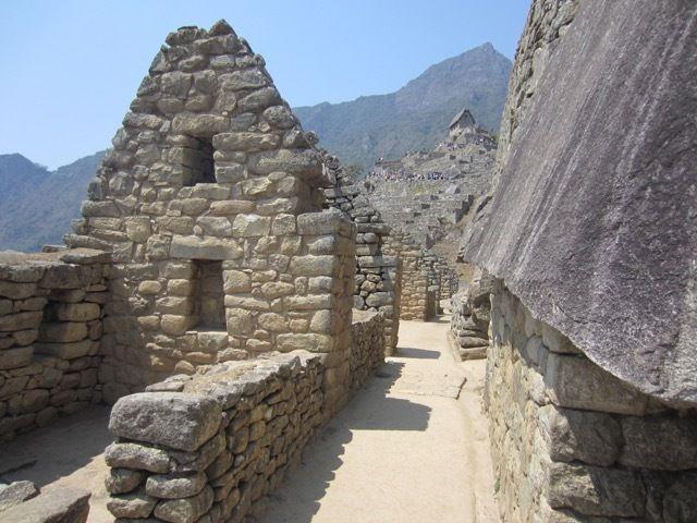 """en regardant vers le sud et le """"corps de garde"""" (batiment avec un toit en arriere-plan, au sommet des terrasses) qui domine le site et surveillait son acces depuis les chemins incas qui arrivaient du sud"""
