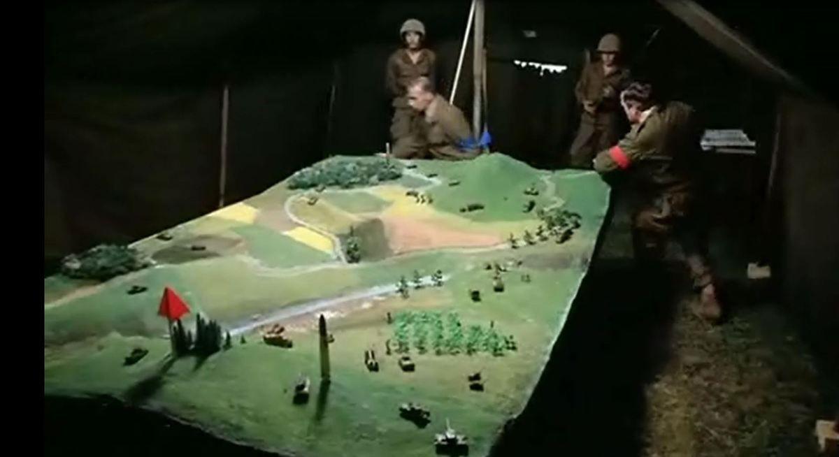 Les officiers se coursent autour de la maquette...