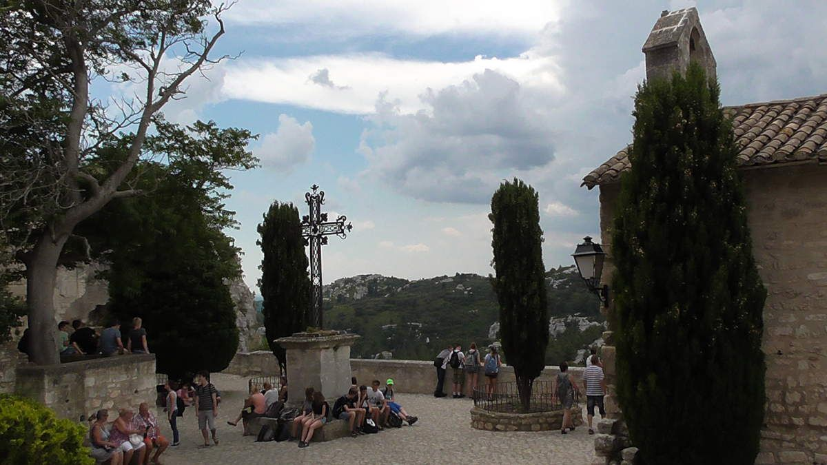 """Cette même Place surplombe un splendide paysage. """"Baux"""" vient de """"Bauç"""" en provençal qui désigne la falaise. La bauxite, minerai d'aluminium, en tire son nom  suite à son exploitation sur le site dès 1820."""