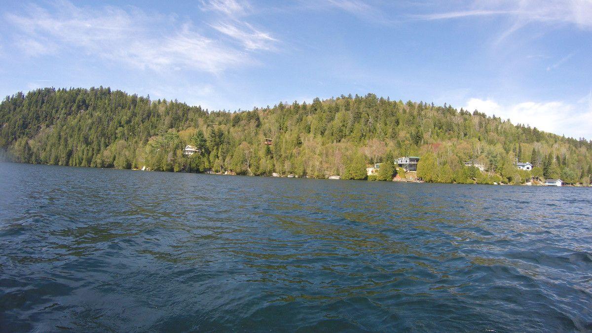 Photo à partir du canot où l'on voit notre chalet rouge au milieu des arbres (clic sur la photo pour agrandir)