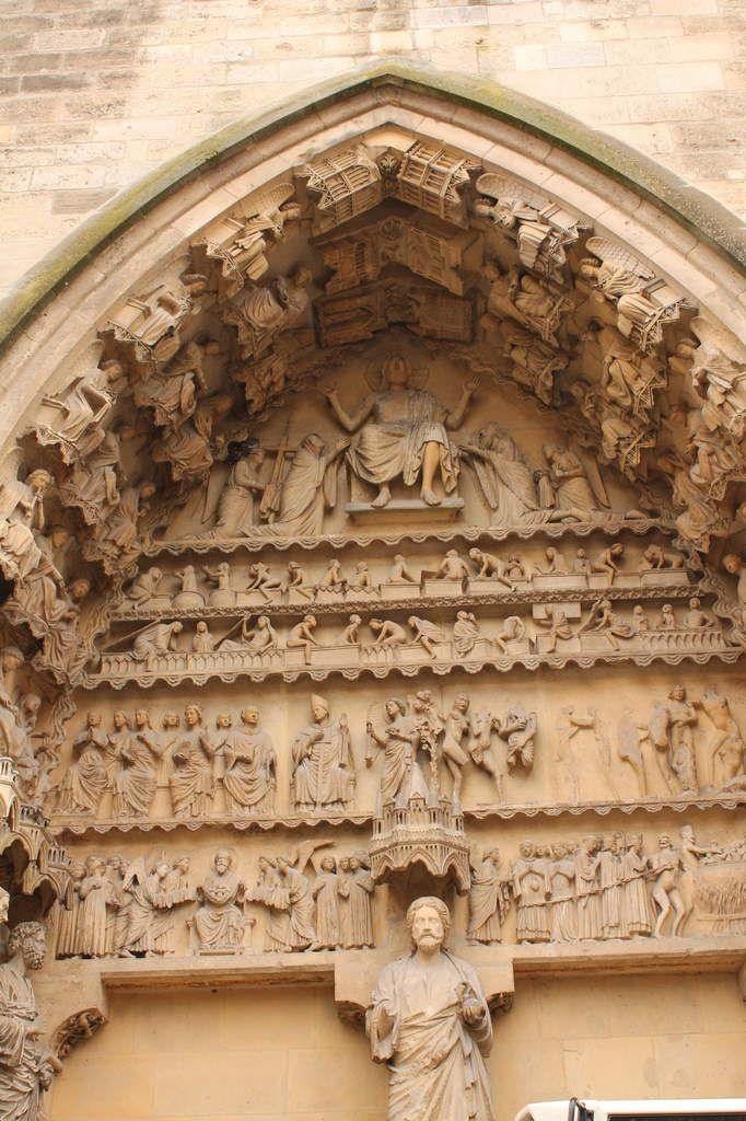 La première photo vous présente le jugement dernier et sa vision sereine de la miséricorde divine. Au premier niveau du tympan, les damnés sont conduits en enfer. Les anges aux mains voilées présentent les âmes sauvées à Abraham, le père des croyants qui les accueille sur un linge,  au  niveau de son giron. Au-dessus, on distingue les efforts des défunts pour sortir (nus) de leurs cercueils. Enfin, au sommet, le Christ en juge. La seconde photo montre un portail entièrement dédié aux saints de l'Eglise de Reims. Au trumeau, saint Calixte. Vous pouvez apercevoir à droite saint Nicaise portant sa tête (saint cépholophore). Plus haut, les miracles de saint Remi chassant les démons, exorcisant une jeune fille et remplissant de vin un tonneau vide.
