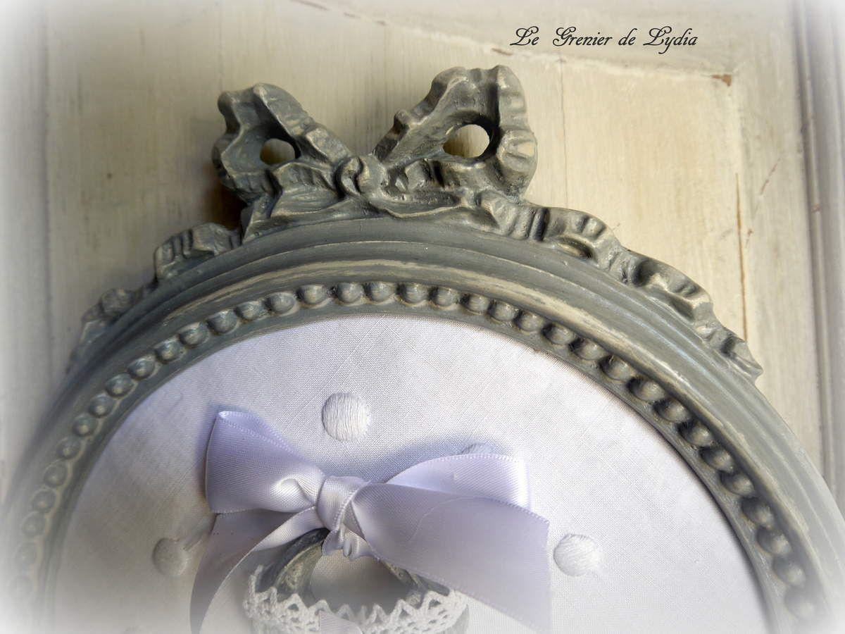 Cadre circulaire à noeud, patiné gris flamand blanchi, fond linge ancien brodé, corset patiné gris flamand, dentelle blanche, noeud et roses de satin blanc. Dimensions  hauteur 30 cm - largeur 26 cm
