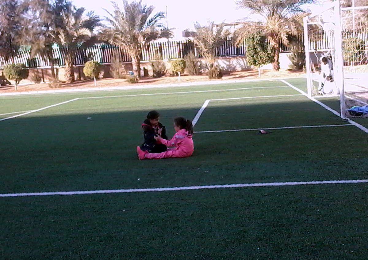 """Les garçons jouent au ballon et les deux fillettes , assises en plein milieu du terrain jouent à autre chose de plus """"intéressant"""""""