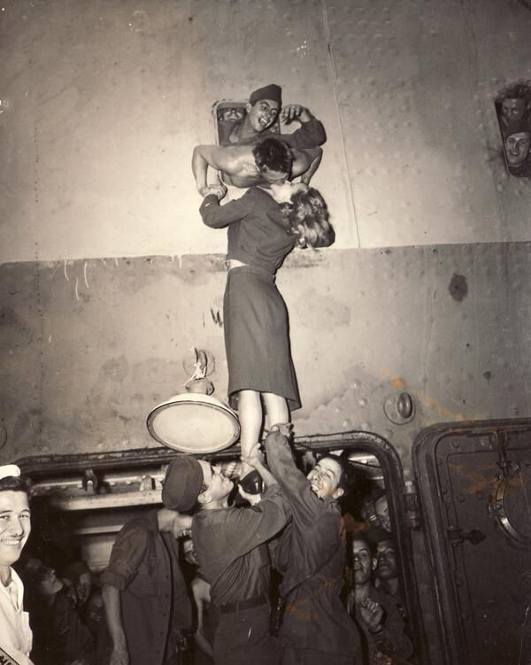 Marlene Dietrich welcomes a soldier returning from World War 2 with a passionate kiss through a porthole, 1945.