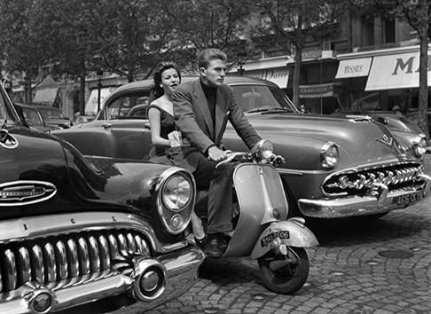 A young couple riding a Vespa on the Champs-Elysées in Paris, 1954