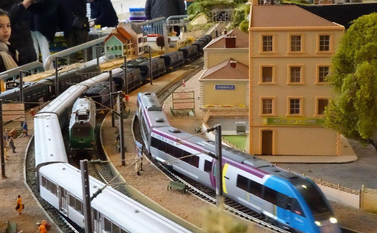 A Courbeville, un train complet de charbon traverse la gare tandis qu'une rame RIO vient de s'immobiliser et qu'un X 72500 démarre en direction de Noisy-le-Petit.