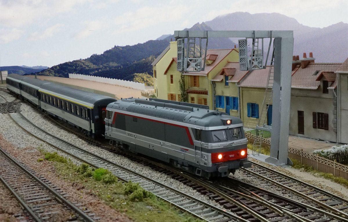 Une courte rame de voitures Corail tractée par la BB 67412 quitte la gare de Courbeville en direction de Verrières.