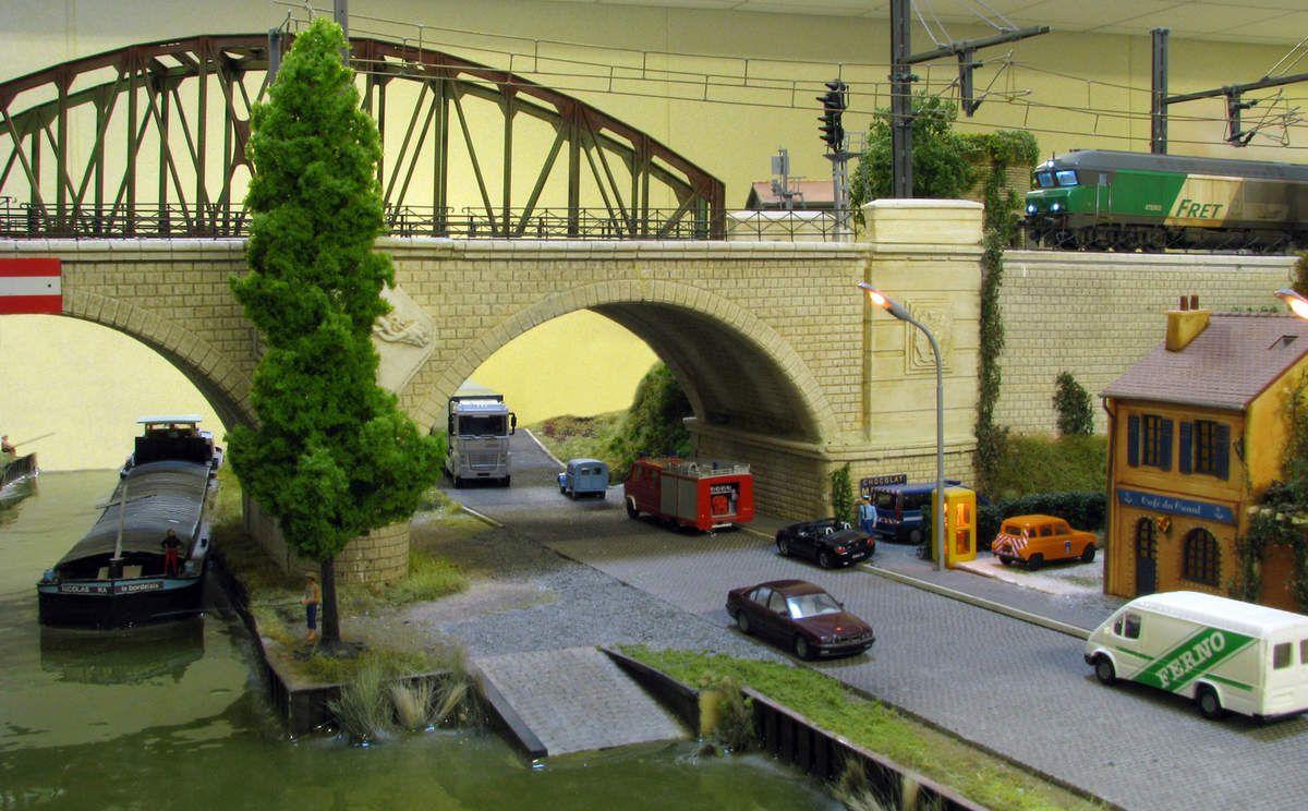 Tandis qu'un train de fret va s'engager sur le pont du canal, un automobiliste imprudemment garé derrière la fourgonnette de la Gendarmerie va devoir s'expliquer.