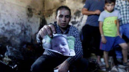 [Légende de la photo] Un proche montre une photo d'un enfant d'un an et demi Ali Dawabsheh, tué quand l'habitation de sa famille a été mise en feu par des extrémistes juifs le 31 juillet 2015 en Cisjordanie occupée