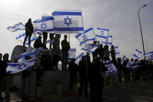 Israelis wave their national flag as a convey transporting the body of Dafna Meir, 38, passes on its way to a cemetery, near the West Bank Jewish settlement of Efrat January 18, 2016. Meir, a female resident of the West Bank settlement of Otniel, was stabbed to death in her home on Sunday when an assailant broke into her house and attacked her, the Israeli army and a local settlement official said. REUTERS/Ronen Zvulun – RTX22UYW