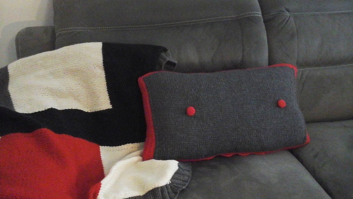 Double face, bordure rouge, zip en bas et 2 boutons recouverts de tricot.