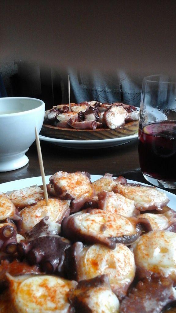 """Puis le pulpo galego bouilli avec laurier et oignon puis rafraîchi, le tout 3 fois. Servi avec un généreux filet d'huile d'olive et saupoudré de pimentón sur une sorte de petitre écuelle semi creuse en bois. Pas question de boire de l'eau, vin blanc du pays servi en bol et tinto de verano. Vous ajoutez du très bon pain pour """"saucer"""" et vous avez un repas délicieux pour la modique somme de 27 euros 50... café con leche compris !"""