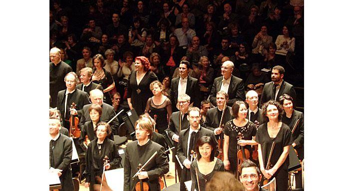 Le chef à gauche, les solistes, les violons, le chef de choeur, et les spectateurs derrière eux