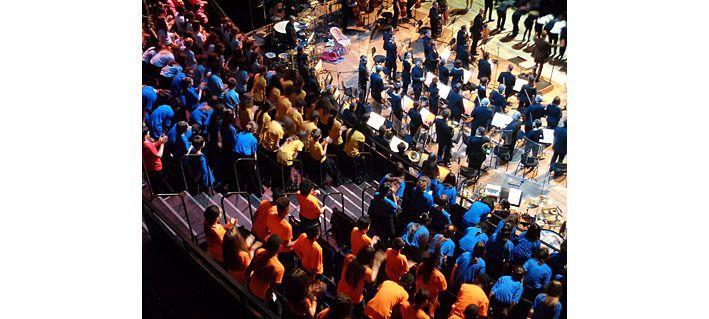Les enfants, en couleurs par école, derrière l'orchestre