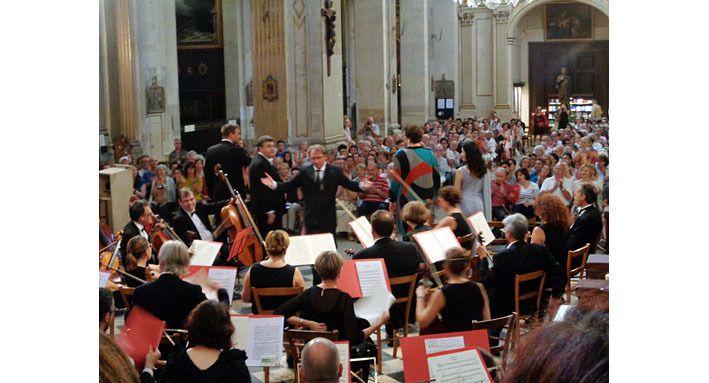 L'orchestre, le chef et les solistes, le public, à la fin du concert