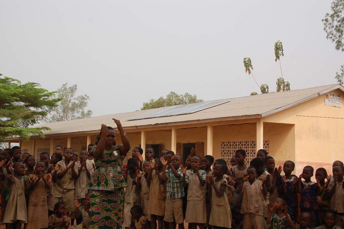 """Mercredi matin 3 février 2016, la délégatiion du CTM est accueillie par les chants de centaines d'enfants alignés dans la grande cour. Congratulés par les enseignants et les autorités locales qui nous remercient par de brefs discours, nous découvrons l'installation des panneaux photovoltaïques et le local des batteries, visitons les 18 salles de classe toutes équipées de tubes led. Ainsi, grâce aux généreux donateurs, 600 élèves peuvent étudier à l'école, même en saison des pluies, et bénéficier de cours de soutien scolaire après la sortie des classes. De même les adultes du quartier suivront des cours d'alphabétisation """"en nocturne"""". S'en suivra une remise des prix aux meilleurs élèves qui recevront divers cadeaux (argent,dictionnaires, cartables, tee-shirts, casquettes etc...). En novembre, une malencontreuse panne a provoqué le désarroi des élèves. Ils ont été rassurés lors de l'intervention efficace d'ESF ce mardi 24 janvier 2017."""