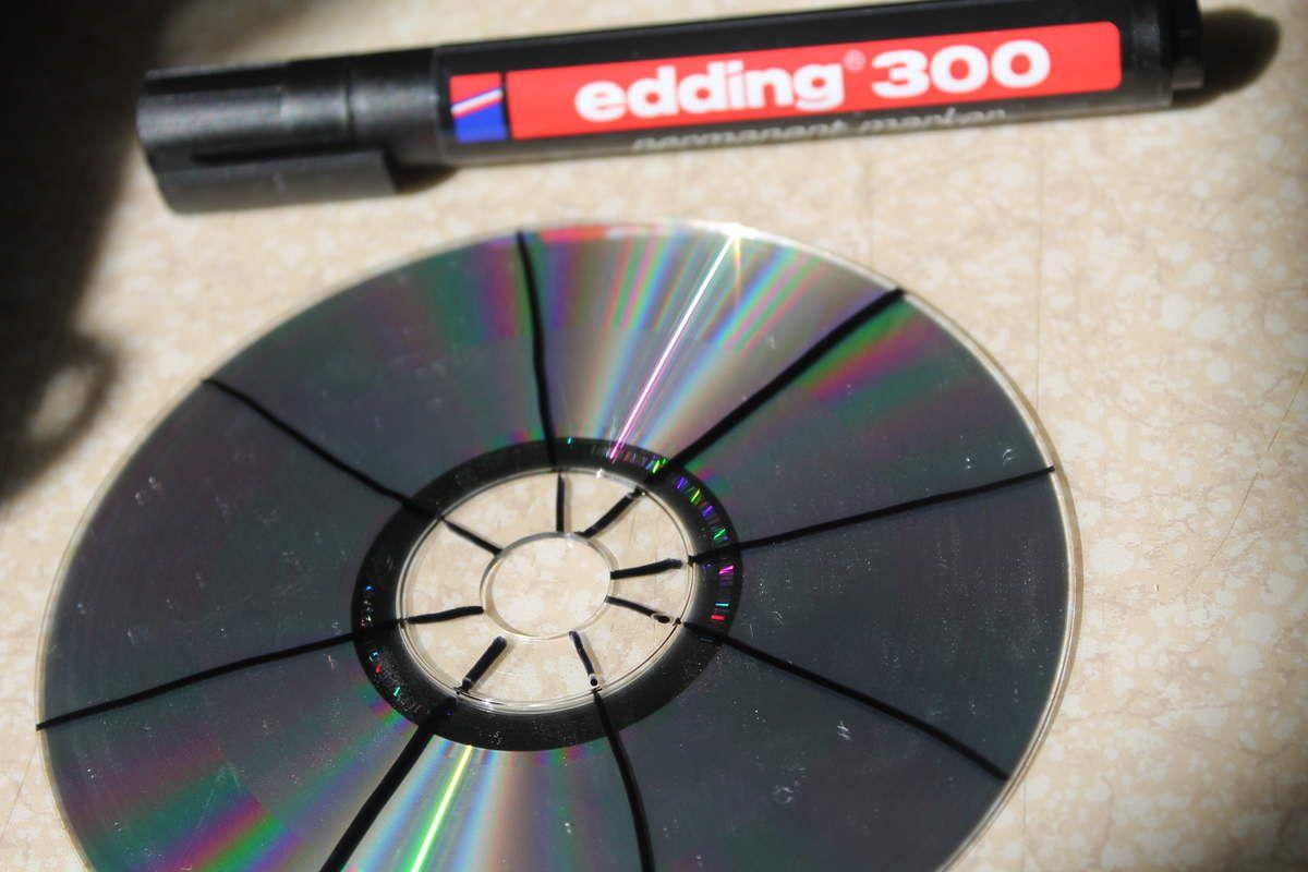 Vous aurez besoin, d'un vieux CD, d'un marqueur, de colle, d'un ciseau, d'un cadre et d'une feuille cartonnée blanche ( je m'excuse, dans la précipitation j'ai oublié de prendre en photo tous le matériel). Tout d'abord, tracé des rayons tout le long du CD