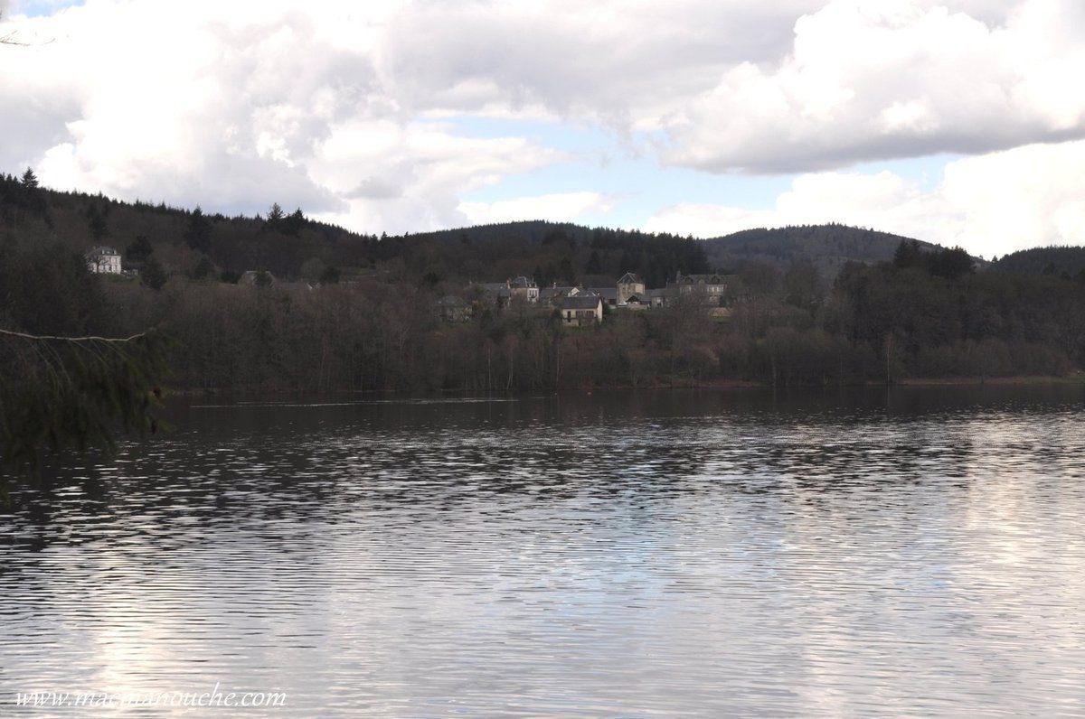 De l'autre côté du lac, on aperçoit quelques maisons du village d'Ambrugeat.