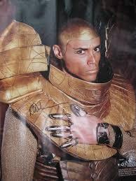 """L'acteur incarnant le Goa'uld """"Aspic"""" dans la série Stargate ( Porte de l'étoile) , est né un 31 Décembre, un jour de l'An. On le voit ici portant un T-shirt ( T = croix Tau) noir avec écrit en doré: 2036. Ce nombre mystérieux renvoi à la date 2036, année lors de laquelle l'astéroïde Aspic pourrait bien entrer en collision avec la Terre ou...la Lune. La gestuelle des mains est un codage utilisé par les hiérophantes du Graal Noir, on la retrouve chez d'autres personnalités et sur des tableaux anciens."""