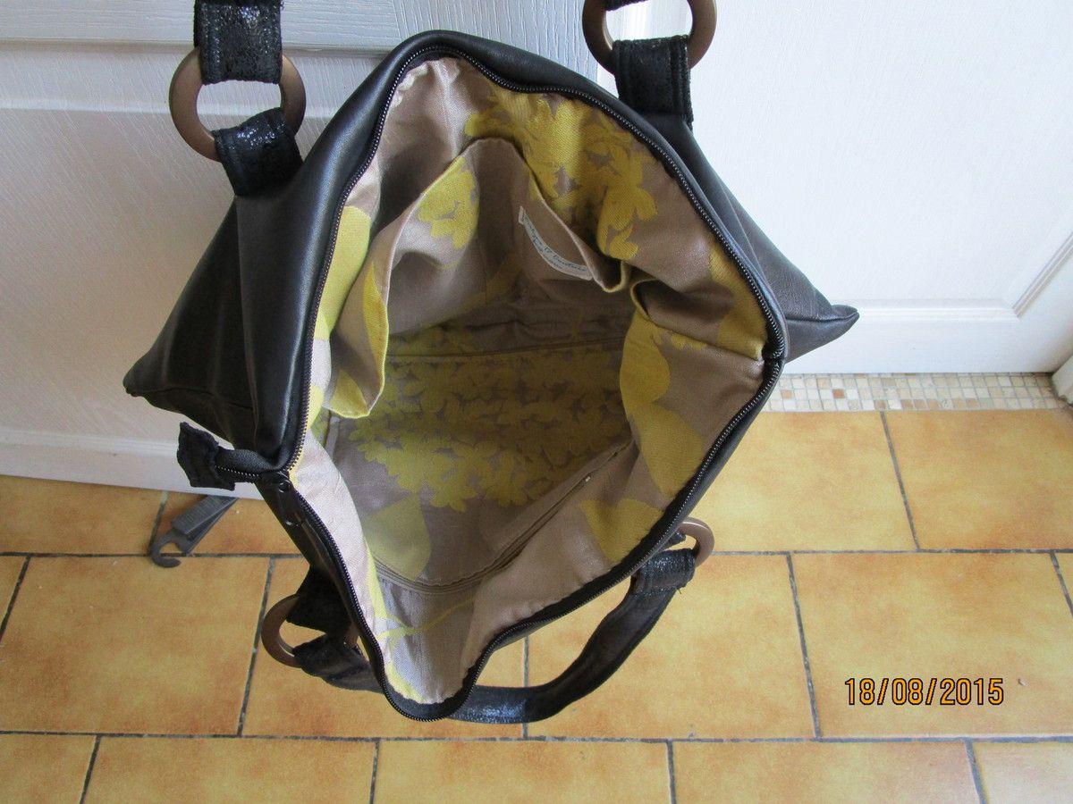 L'intérieur et en satin jaune et gris,1poche zippèe et 2 autres ouvertes ,les 2 sacs sont fermès avec des zip