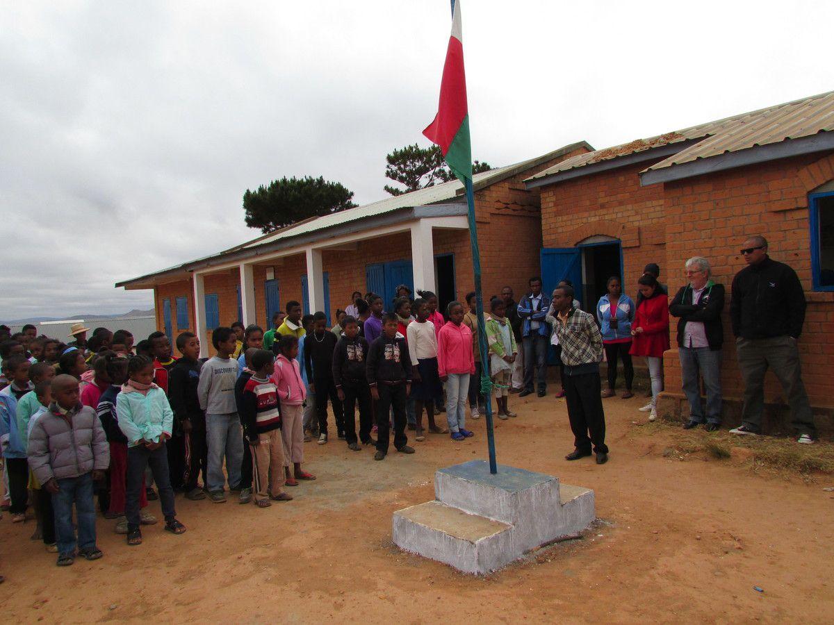 Levée des couleurs accompagné de l'hymne national par les enfants en présence de nombreux parents.