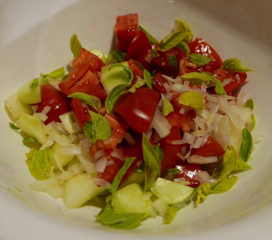 Coupez les tomates, les concombres, l'oignon et le basilic. Reservez...