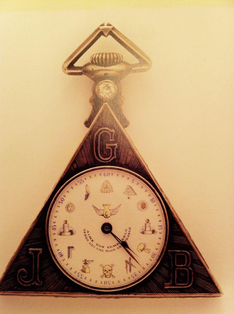 Montre Triangulaire en argent ornée de symboles et préceptes maçonniques sur le cadran, et richement ornée d'un motif de temple sous oeil divin au verso Suisse 1925
