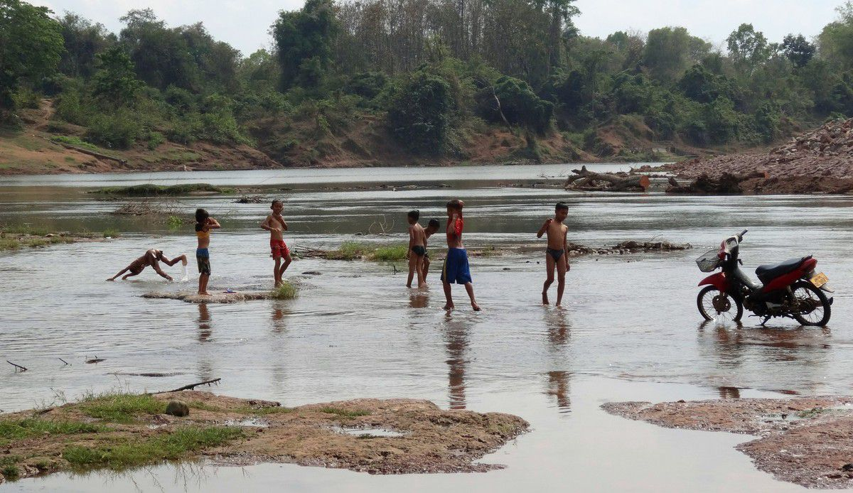d'autres enfants font sécher un filet de pêche.