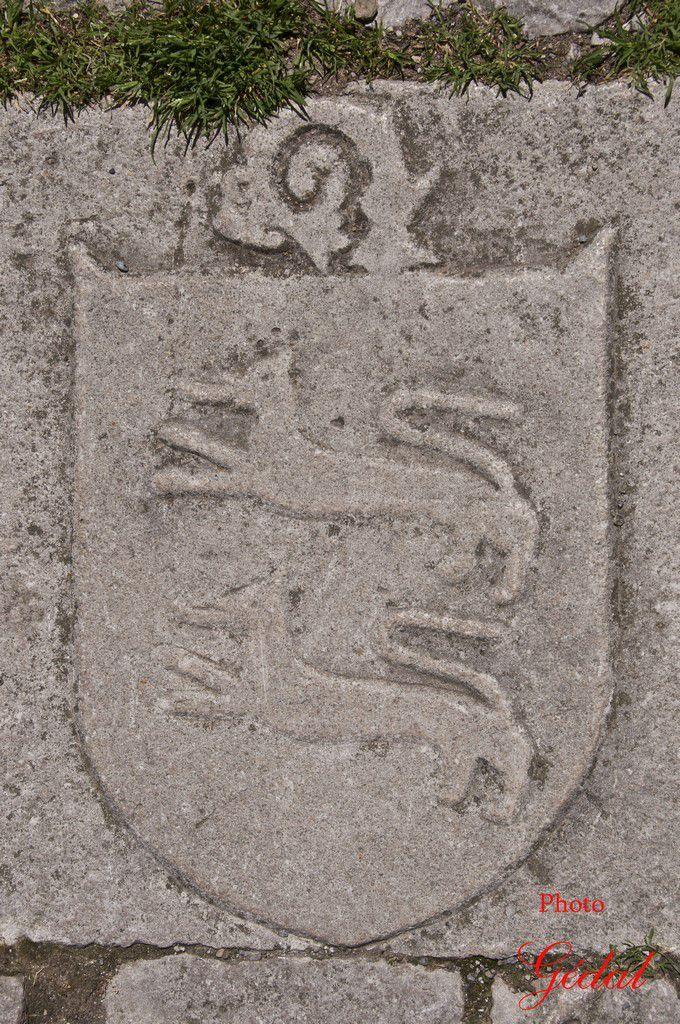 Écusson sculpté sur une pierre, à l'entrée de la porte principale.