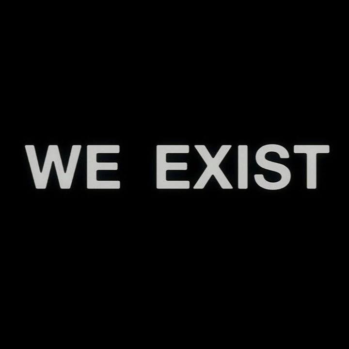 """traduction du texte de l'image écrit en anglais : """"nous existons"""" écrit en gris sur un fond entièrement noir."""