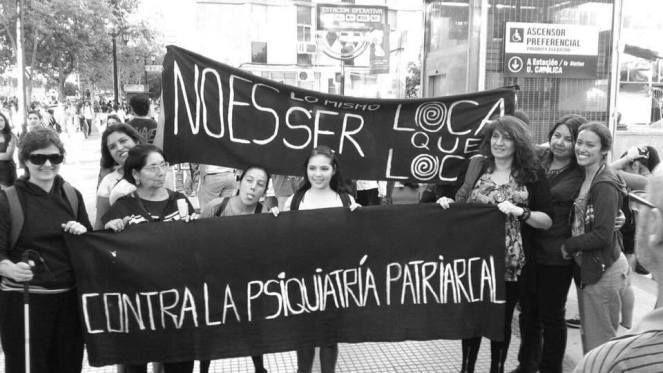 Image: un groupe de femmes, pendant une manifestation, tient des banderoles sur lesquelles on peut lire : ''être folle ce n'est pas comme être fou'' et ''contre la psychiatrie patriarcale''