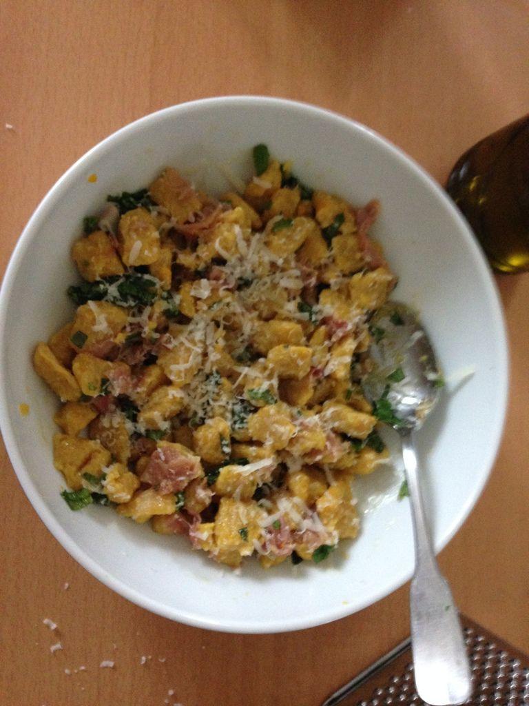 Gnocchis de potiron servis ici avec un filet d'huile d'olive, des feuilles de basilic, et quelques tranches de pancetta grillées à la poêle