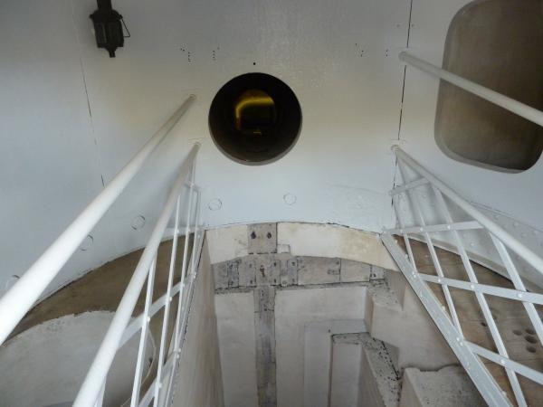 Intérieur d'un tourelle de chargement, avec le puits du monte-charge en bas et le logement du refouloir hydraulique en face