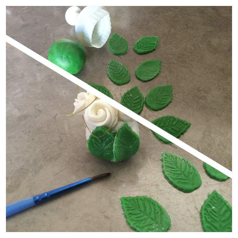 Préparez les feuilles de vos roses en les découpant à l'emporte-pièce dans la pâte à sucre verte. Collez-les en les superposant légèrement à l'aide d'un pinceau et d'eau sur la partie basse du support.