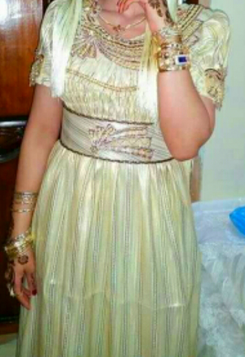 Blouza al Mensouj, Robe confectionnée avec du tissu tissé au fil d or, une étoffe précieuse et très cher, uniquement destinée à la mariée qu' elle portera à chaque mariage
