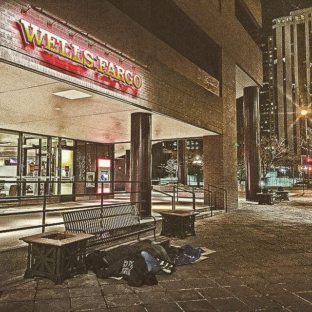 16 street mall in Denver, CO 2016. A homeless man lays in front of Wells Fargo.