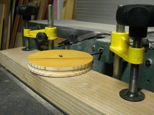 Je passe ensuite à la partie la plus improbable pour moi (car je ne dispose pas de tour à bois), la réalisation des roues. Je découpe grossièrement quatre disques de 13 cm de diamètre que je finalise en les passant au disque à poncer monté sur une mortaiseuse !!! Ben oui c'est pas fait pour ça à la base mais bon... Ca tourne trop vite et mon disque à poncer a fumé !!! Le mieux c'est d'utiliser une perceuse montée en fixe sur une table&#x3B; à défaut de tour à bois. Ensuite je creuse une feuillure au centre de l'épaisseur du disque pour y insérer un gros caoutchouc carré (pas top non plus mais je n'ai pas trouvé de joint torique de ce diamètre et gros de plus de 5mm) !!! On fait avec ce qu'on a, c'est l'idée de départ.