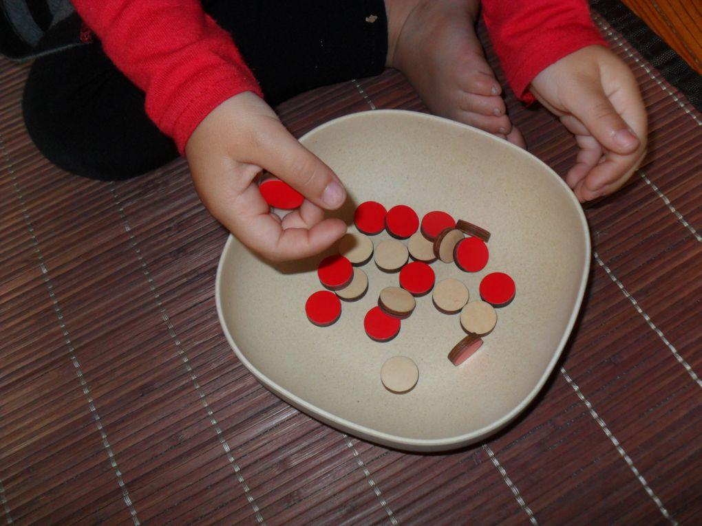 Sur un tapis, j'avais installé ces cartes dans l'ordre. Alana devait poser le bon nombre de jetons. Cette activité est simple, les enfants peuvent la faire de différentes manières : seulement poser les jetons sur les points noirs &#x3B; ou compter le nombre de points sur chaque carte avant de poser les jetons &#x3B; ou essayer de reconnaître le chiffre et mettre le bon nombre de jetons ensuite. Alana a reconnu les 4 premiers chiffres, mais a dû compter le nombre de points pour 5 et 6.