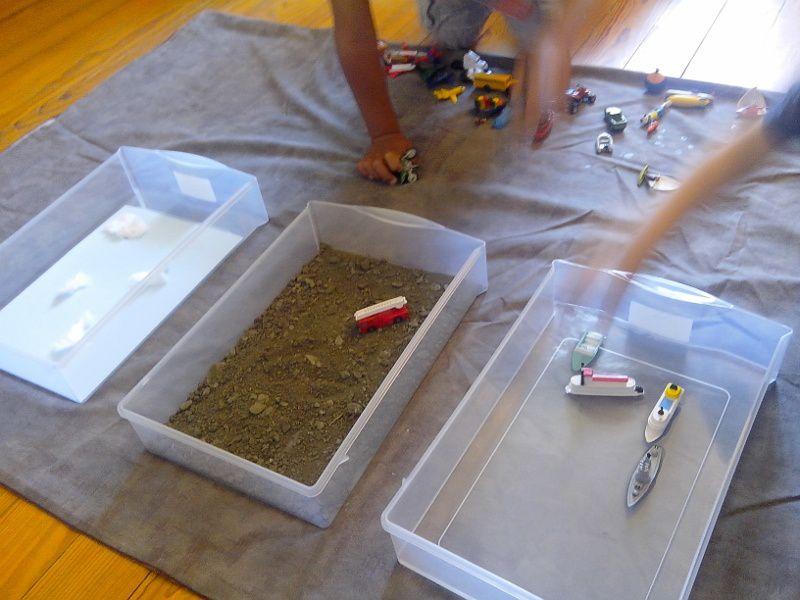 """Eau-terre-air : Trois bacs : dans le premier, de l'eau, dans le deuxième, de la terre et dans le troisième, une feuille bleue et des bouts de cotons pour symboliser le ciel et les nuages. Les enfants ont placé les figurines dans les différents bacs, selon leur """"milieu de vie"""". Ils ont bien sûr pu manipuler longemps le matériel."""