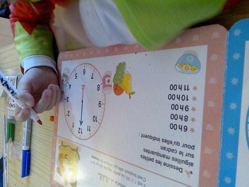 Les premiers exercices du livre-ardoise sur l'apprentissage de l'heure.